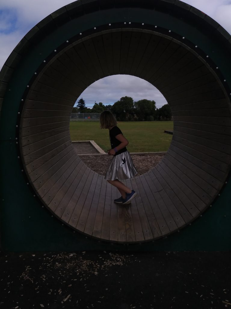 A girl running on a playground tube like a hamster wheel