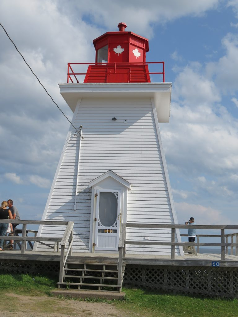 A white wooden lighthouse with a red top