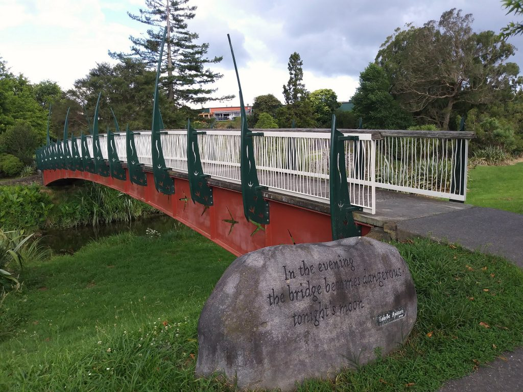 Red bridge with white rails and green decorative posts, across a stream. In front, a rock with a haiku.