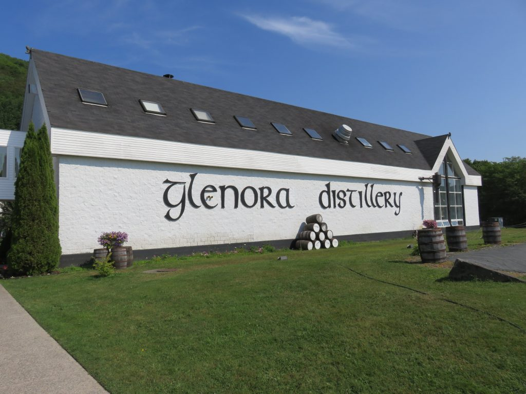A white building with Glenora Distillery written on it in a Celtic font