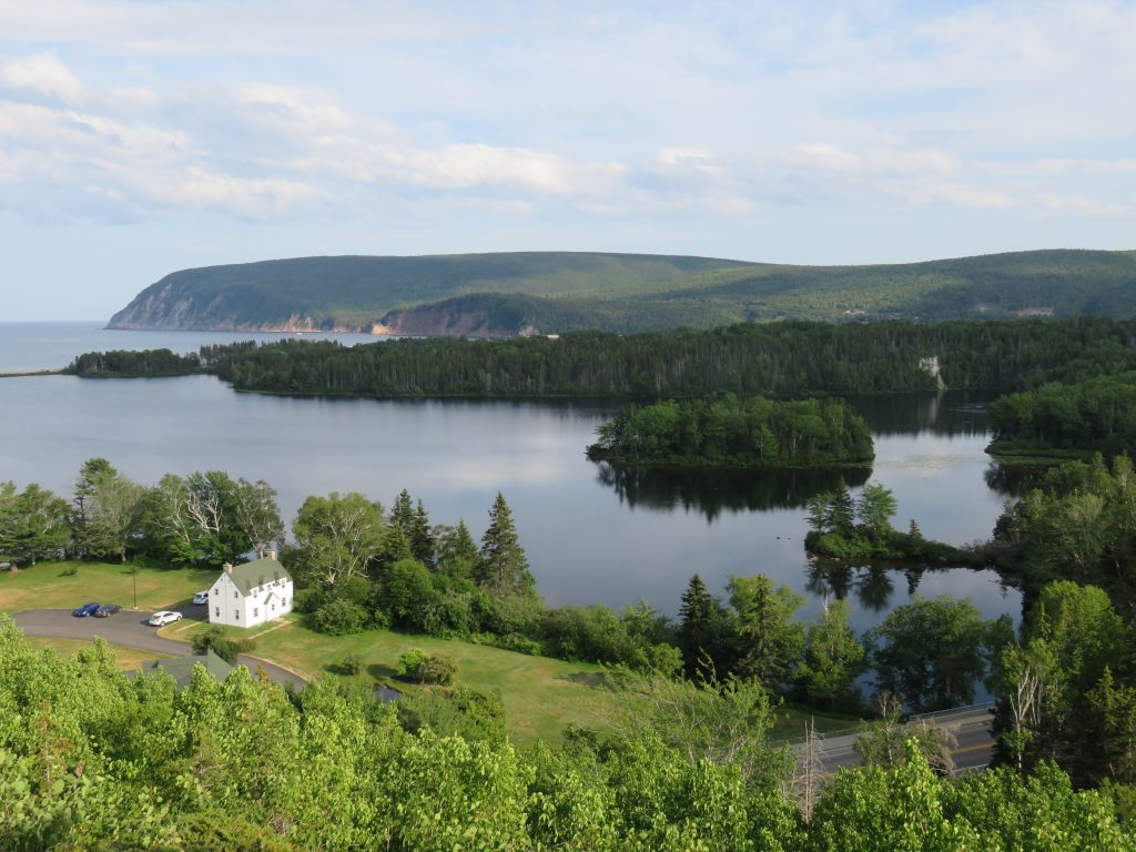 View of a lake with a wooded island and cliffs in the distance.