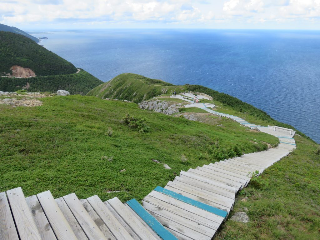 Wooden staircase leading down to a viewpoint looking out over a cliff to the ocean.