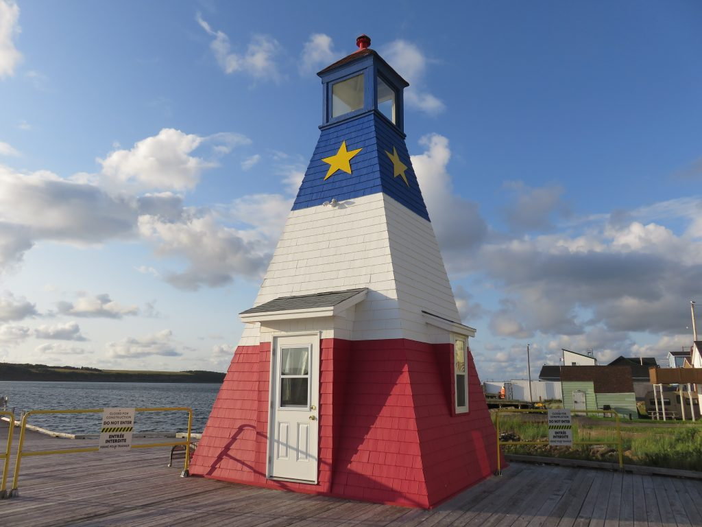 Lighthouse painted red, white, and blue with a yellow star