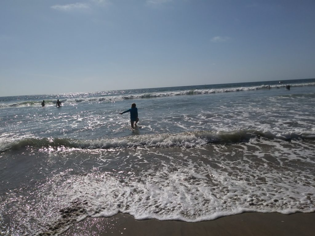 A girl splashes in shallow waves at the beach.
