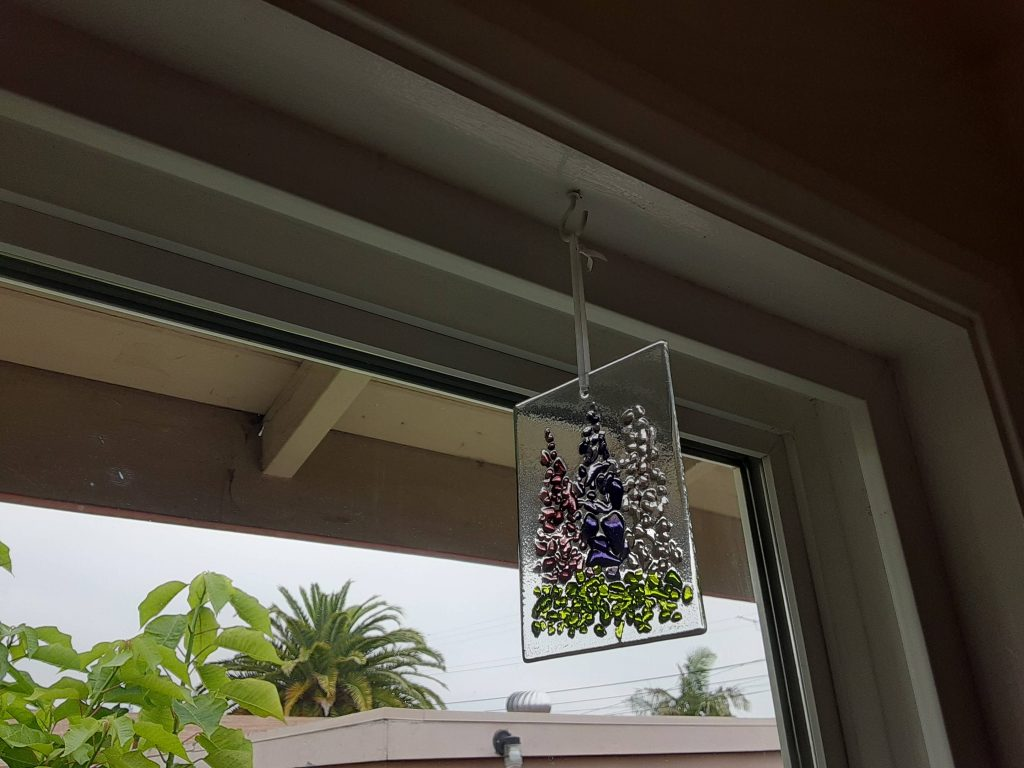 A rectangle of clear glass with three shades of purple flowers on it.