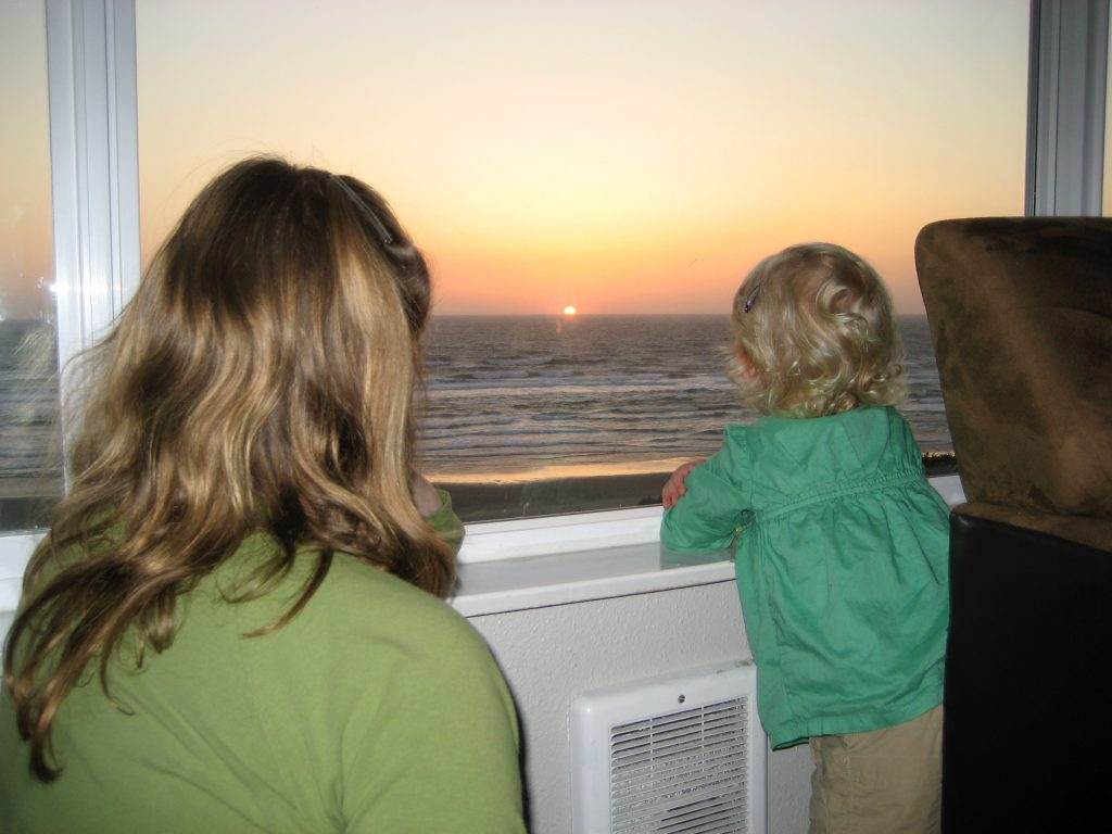A woman and a toddler watch the sun set into the ocean outside a window