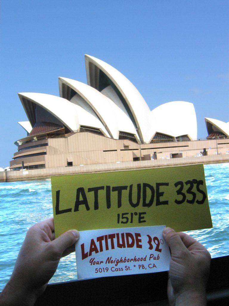 Sydney Opera House with turquoise water and a handmade sign showing Latitude 33 degrees S in the foreground