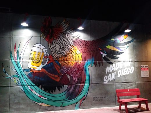 A mural of a rooster with a beer