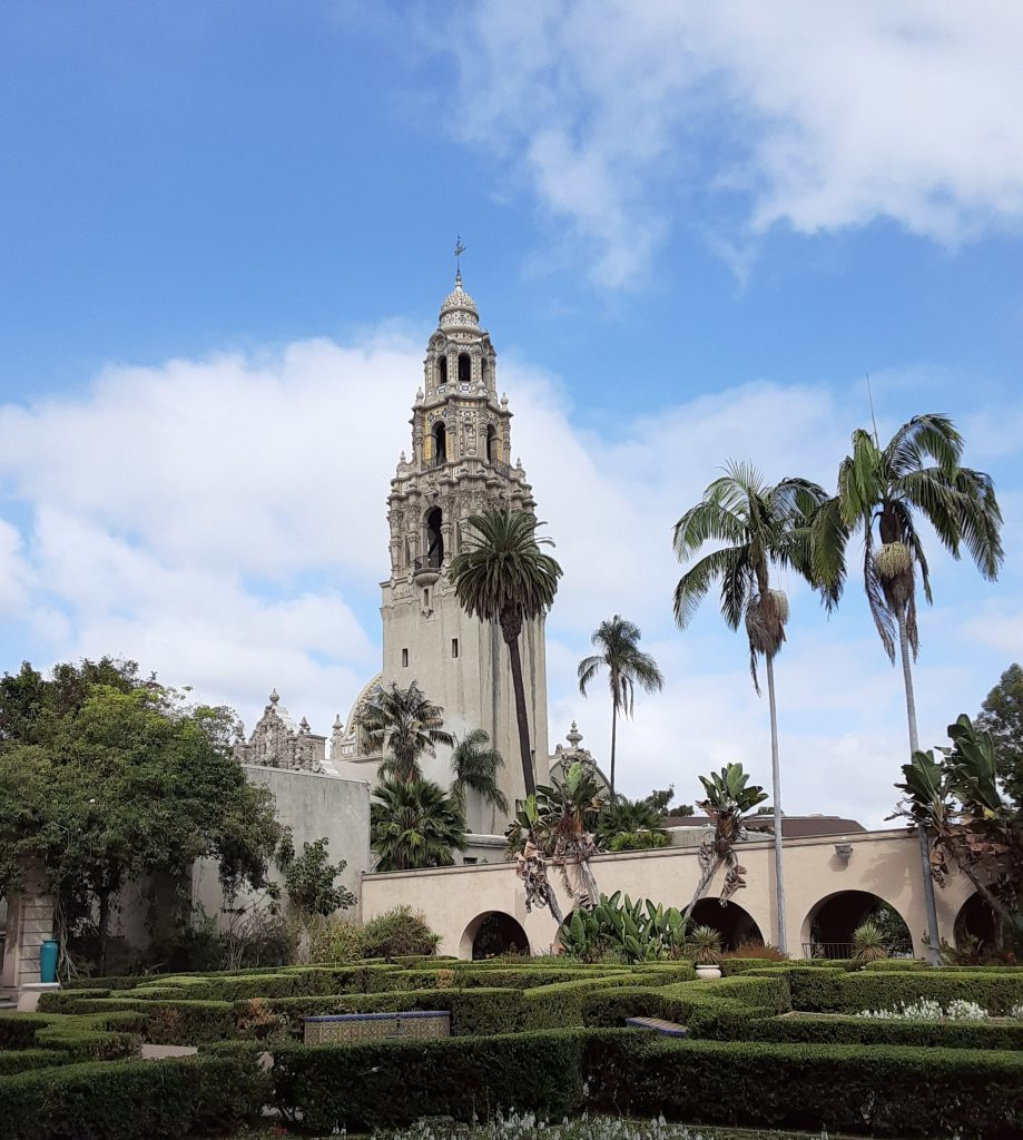 Bell tower and palm trees with a hedge maze in the foreground
