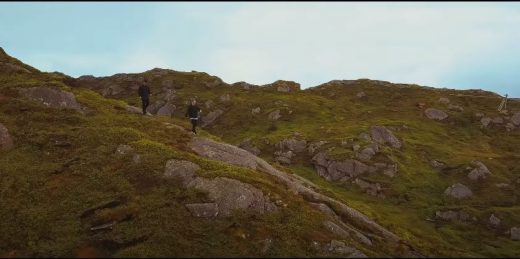 Two men hiking in mountains with grass and granite groundcover