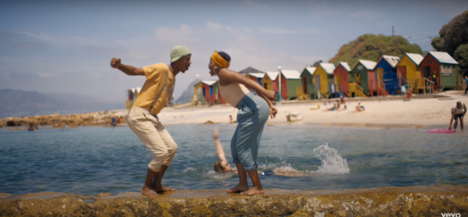 screenshot from music video Til I Found You, with two dancers on the beach